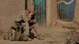 A U.S. Marine from 3rd Battalion, 6th Marine Regiment sits alone after a patrol in Marjah in Afghanistan's Helmand province Friday, Feb. 19, 2010.