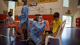 طاقم طبي يختبر الأطفال الإسرائيليين في ملعب لكرة السلة تحول إلى مركز لفحص فيروس كورونا في إسرائيل.