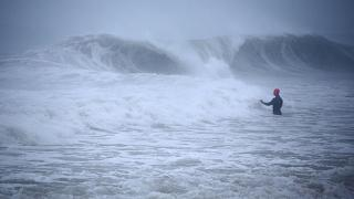Matt Prue, from Stonington, Conn., walks out into the Atlantic Ocean to body surf the waves from Tropical Storm Henri as it approaches Westerly, R.I., Sunday, Aug. 22, 2021.