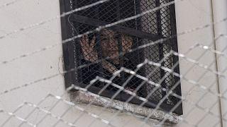 La expresidenta interina de Bolivia, Jeanine Anez, saluda desde una ventana de la cárcel de mujeres de Miraflores en La Paz, Bolivia, el 18 de agosto de 2021.