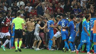 Fans invade the pitch during the French L1 football match between OGC Nice and Olympique de Marseille (OM) at the Allianz Riviera stadium in Nice, France on August 22, 2021.