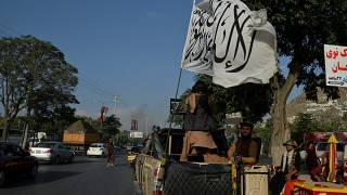 Taliban fighters travel on a vehicle mounted with the Taliban flag in the Karte Mamorin area of Kabul on August 22, 2021
