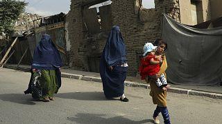 Burkába öltözött nők és gyerekek sétálnak egy kabuli utcán