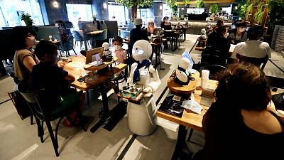 In this picture taken on August 17, 2021, a humanoid robot delivers drinks to customers at the Dawn Café in Tokyo.