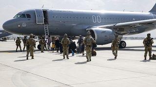 Magyar katonák kimentendő afgán, magyar és amerikai állampolgárokat kísérnek a magyar légierő gépéhez a kabuli reptéren