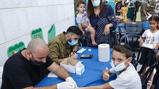أطفال إسرائيليون يخضعون لاختبار الأجسام المضادة لكوفيدـ19 في مدينة نتانيا الساحلية، في 22 أغسطس 2021، قبل بدء العام الدراسي الجديد.