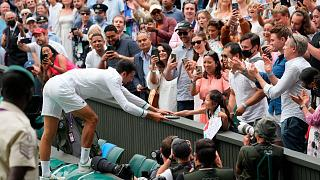 Serbia's Novak Djokovic presents his tennis racquet to a young fan after winning the men's singles final of the Wimbledon Tennis Championships in London, July 11, 2021.