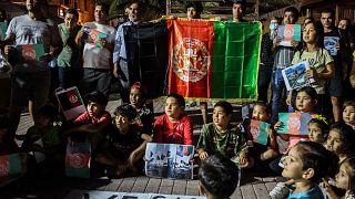 مهاجرون أفغان يحملون العلم الأفغاني أثناء احتجاجهم على سيطرة طالبان على أفغانستان، في جزيرة ليسبوس اليونانية، 16 أغسطس 2021