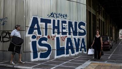 """Pedestrians walk past grafitti """"Athens is Lava"""" in central Athens on July 12, 2017."""