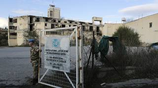A UN soldier stands by a gate that leads inside the UN buffer zone, Green Line, that divides the Greek, south, and Turkish, north on Jan. 4, 2017.