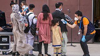 Varios sanitarios toman la temperatura a evacuados afganos a su llegada a Torrejón de Ardoz, en Madrid