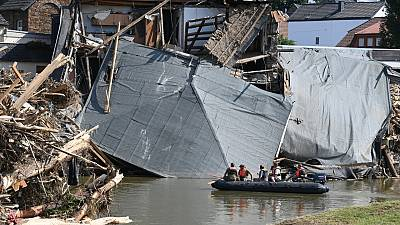 Military personnel on a boat on the Ahr river as the roof of a damaged house hangs on the water in Rech, western Germany, on July 21, 2021, after floods hit the region.