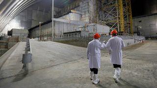 Des employés devant l'ancien réacteur de la centrale nucléaire de Tchernobyl recouvert d'un abri récent, le 15 avril 2021
