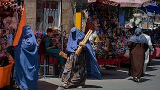 Taliban'ın ülkeyi ele geçirmesinin ardından burka giyinen Afgan kadınlar pazar alanında alışveriş yapıyor
