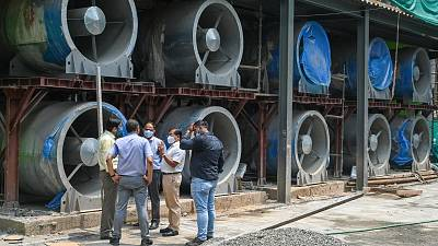 Officials talk next to large fans at the construction site of a 25-metre (82 foot) high smog tower.