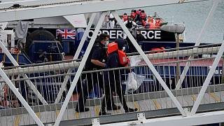 A suspected migrant disembarks after being picked up in the Channel by a British border force vessel in Dover.