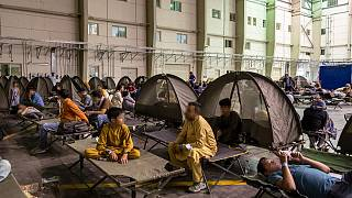 """Refugees wait at an evacuation centre after they left Kabul as part of the operation """"Apagan"""" at the French military air base of Al Dhafra, near Abu Dhabi, on August 23, 2021."""