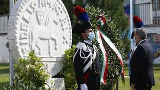 Italian Premier Mario Draghi pays his respects by a wreath on the monument in Amatrice.