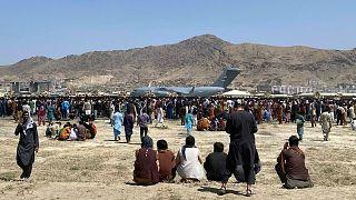 Des centaines de personnes se rassemblant près d'un avion de transport C-17 de l'armée de l'air américaine, sur l'aéroport international de Kaboul, en Afghanistan, le 16 août