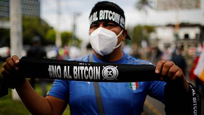 """A man sells badanas that reads """"No to Bitcoin"""" in a war veterans protest to ask for better pensions and against the use of Bitcoin as legal tender in San Salvador, El Salvador"""