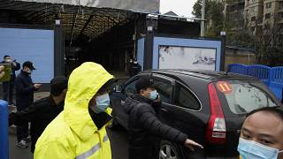 Security personnel clear the way for a convoy of the World Health Organization team to enter the Huanan Seafood Market in Wuhan in January 2021.