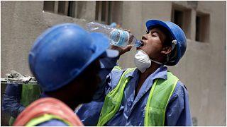 عامل نيبالي يشرب الماء أثناء عمله في أحد المشاريع بالعاصمة القطرية الدوحة