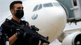 یک مامور ژاندارمری فرانسه در کنار هواپیمای حامل افغانهای منتقل شده به فرودگاه شارل دو گُل پاریس