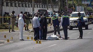 تقف قوات الأمن وخبراء الطب الشرعي بالقرب من جثة مغطاة جزئيًا في شارع بالقرب من السفارة الفرنسية في دار السلام، تنزانيا، الأربعاء 25 أغسطس 2021