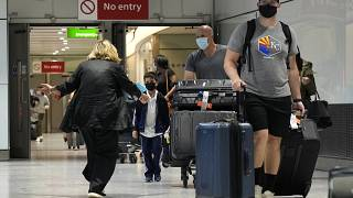 A woman runs to greet a child as passengers arrive at Terminal 5 of Heathrow Airport in London, Monday, Aug. 2, 2021.