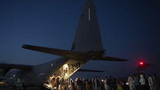 Cette photo prise le 26 août 2021 montre des personnes embarquant dans un avion militaire français à l'aéroport de Kaboul
