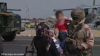 Image d'un soldat français tenant par la main un enfant afghan sur l'aéroport de Kaboul, Afghanistan, 23 août 2021