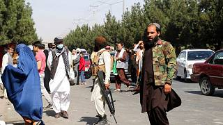 Taliban fighters stand guard outside the airport after Thursday's deadly attacks