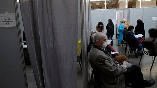 People wait to receive Pfizer's COVID-19 vaccine at a vaccination site in Paris, Saturday, March 6, 2021.