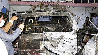 Des journalistes afghans prennent en photo un véhicule détruit à Kaboul le 29 août 2021