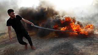 Égő gumiabroncsot húzó palesztin férfi egy korábbi tüntetésen