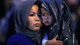 Egy afgán nő gyermekével Athén kikötőjében miután oda szállították a görögországi Leszbosz szigetén található menekülttáborból 2019 október 7-én