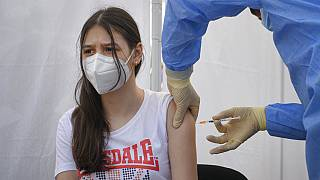 A girl gets a Pfizer BioNTech COVID-19 vaccine in Bucharest