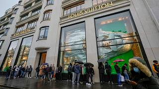 People line up as they wait to get in the Louis Vuitton shop on the Champs Elysee avenue in Paris, Wednesday, May 19, 2021