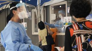 A medical worker in a booth takes a nasal sample from a woman during coronavirus testing at a makeshift testing site in Seoul