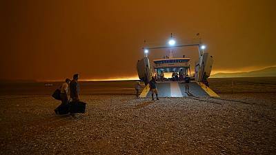 Smoke spreads over the sea as local residents and tourists use a ferry to evacuate Pefki village on Evia island on August 8 2021.