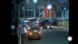 Fermo immagine di una telecamera di videosorveglianza. Si vedono due uomini stesi sul cofano di un'auto in fuga