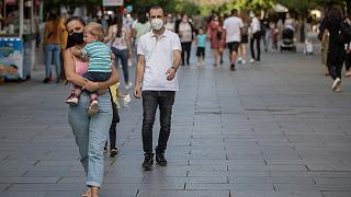 Pedestrians wear face masks through Mother Teresa square in Kosovo's capital Pristina.