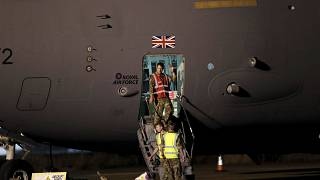 British military personnel depart a C-17 aircraft at RAF Brize Norton, Oxfordshire, late Sunday, Aug. 29, 2021.