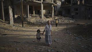 طفلتان يسرن في شارع تضرر بشدة جراء غارة إسرائيلي�� في بيت حانون، قطاع غزة.