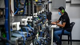 An employee inspects computers used to mine Bitcoin at the mining showroom of the Doctor Miner company in Caracas on August 18, 2021.