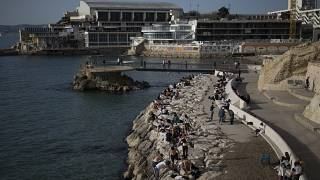 Sunbathers sit by the Plage des Catalans in Marseille, southern France, Friday, April 2, 2021.