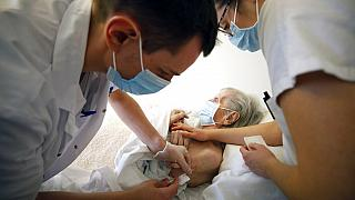 In this Jan. 6, 2021, file photo, Dr. Cedric Waechter, left, administers the Pfizer-BioNTech COVID-19 vaccine to a resident of the Bois Fleuris nursing home in Strasbourg