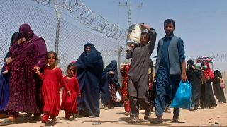 Afghans entering Pakistan through a common border crossing point in Chaman
