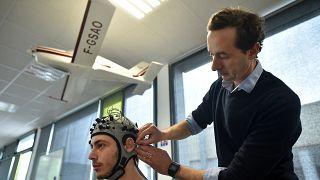 مدرس علم الأعصاب ومدير مختبر الأبحاث في المعهد العالي للملاحة الجوية والفضاء يقوم باختبار علم الأعصاب في محاكي قمرة القيادة، في 26 مارس 2018 في تولوز، جنوب فرنسا.