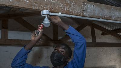 self-taught electricity producer Colrerd Nkosi fixes a bulb in a Standard Eight Class to light the classroom with electricity generated by Nkosi's hydro-powered turbine.
